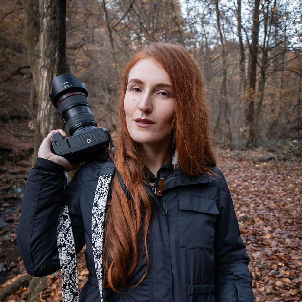 Fotografin Natalia Le Fay. Sie hat lange rote Haare und trägt eine schwarze Haukland 5-in-1 Jacke. Sie hat ihre Kamera in der rechten Hand und steht im Herbstwald.